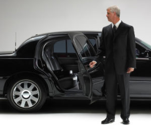 Chauffeur opening Limo car door. Isolated against white.